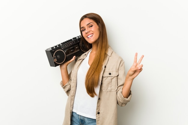 Young caucasian woman holding a guetto blaster joyful and carefree showing a peace symbol with fingers.
