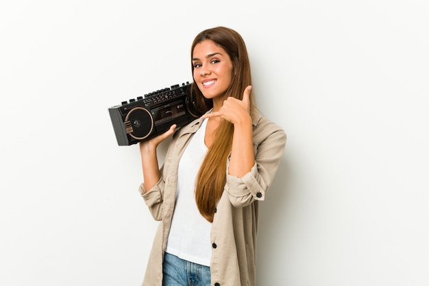 Young caucasian woman holding a guetto blaster showing a mobile phone call gesture with fingers.