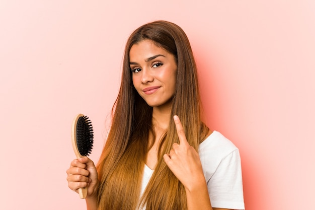 Young caucasian woman holding an hairbrush pointing with finger at you as if inviting come closer.