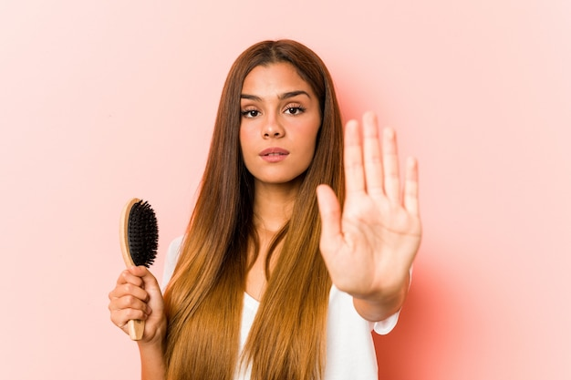 Young caucasian woman holding an hairbrush standing with outstretched hand showing stop sign, preventing you.