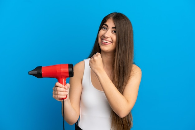 Young caucasian woman holding a hairdryer isolated on blue background celebrating a victory