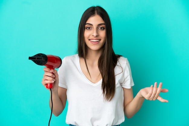 Young caucasian woman holding a hairdryer isolated on blue background with shocked facial expression