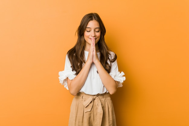 Young caucasian woman holding hands in pray near mouth, feels confident.