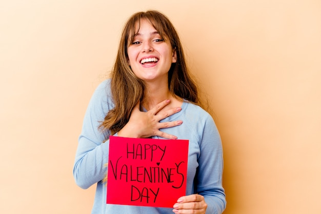 Young caucasian woman holding a happy valentines day isolated laughs out loudly keeping hand on chest.