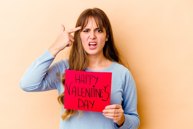 Young caucasian woman holding a happy valentines day isolated showing a disappointment gesture with forefinger.