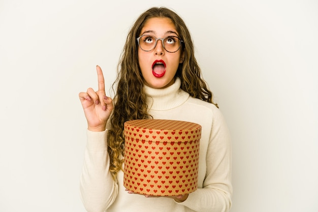Young caucasian woman holding a heart valentines day box isolated pointing upside with opened mouth.