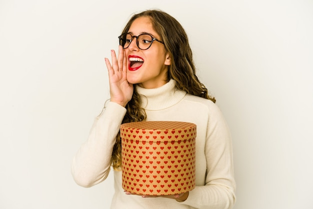 Young caucasian woman holding a heart valentines day box isolated shouting and holding palm near opened mouth.