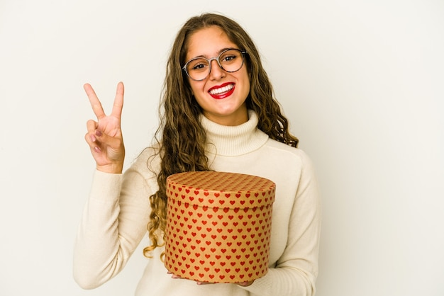 Young caucasian woman holding a heart valentines day box isolated showing number two with fingers.