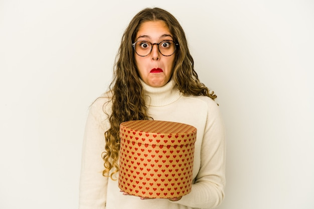 Young caucasian woman holding a heart valentines day box isolated shrugs shoulders and open eyes confused.