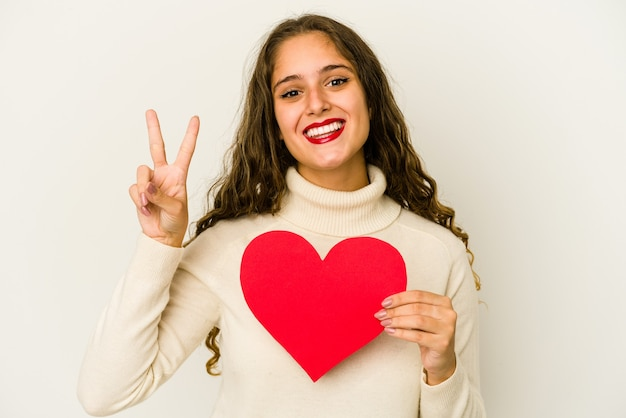 Young caucasian woman holding a heart valentines day shape isolated showing number two with fingers.