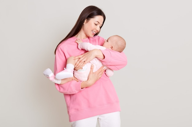 Young caucasian woman holding her daughter in hands and looking at her baby, mother hugging her baby, expresses love and gentle, wearing casual jumper and pants, isolated over white wall.