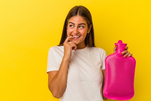 Young caucasian woman holding a hot bottle water isolated on yellow wall relaxed thinking about something looking at a copy space.