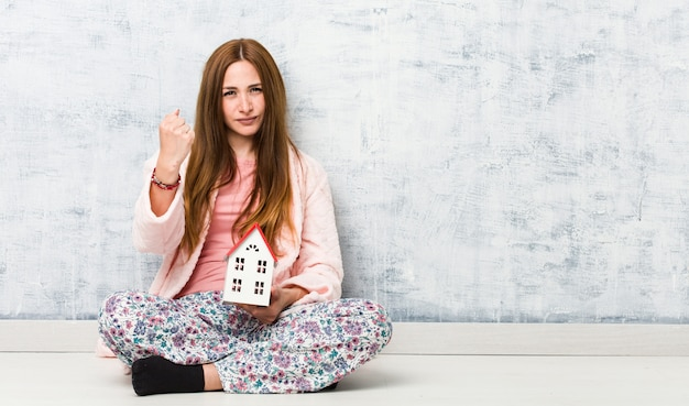 Young caucasian woman holding a house icon showing fist to camera, aggressive facial expression.
