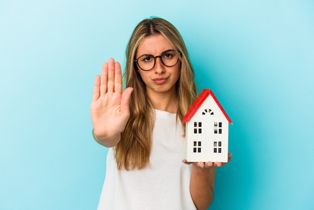 Young caucasian woman holding a house model isolated on blue background standing with outstretched hand showing stop sign, preventing you.