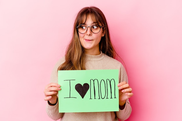 Young caucasian woman holding a i love mom isolated confused