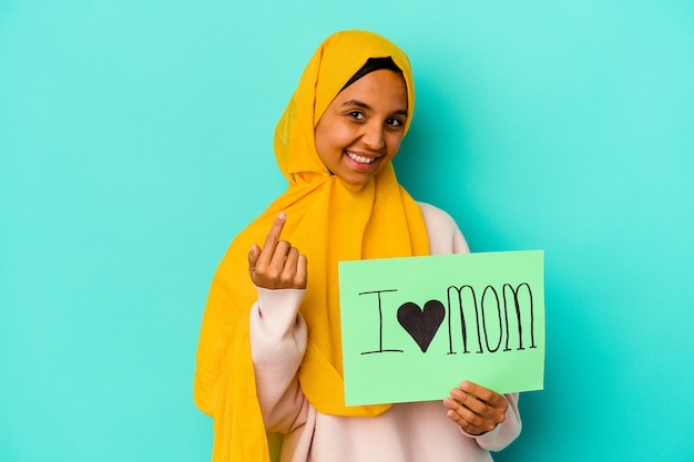 Young caucasian woman holding a i love mom isolated on pink background pointing with finger at you as if inviting come closer.