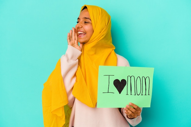Young caucasian woman holding a i love mom isolated on pink background shouting and holding palm near opened mouth.