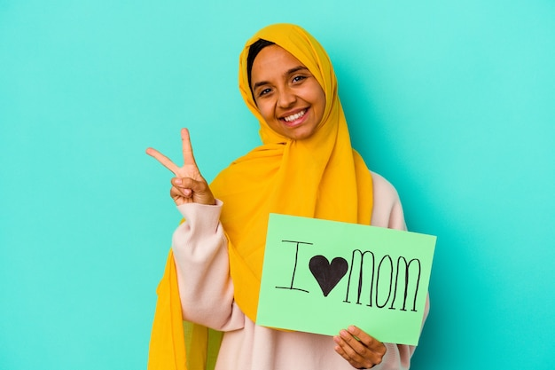 Young caucasian woman holding a i love mom isolated on pink wall joyful and carefree showing a peace symbol with fingers.