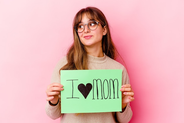 Young caucasian woman holding a i love mom isolated