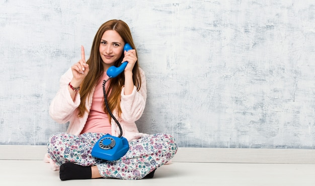 Young caucasian woman holding landline showing number one with finger.