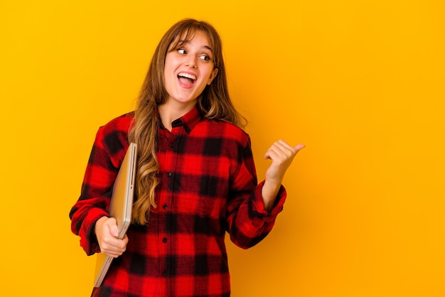 Young caucasian woman holding a laptop isolated points with thumb finger away, laughing and carefree.