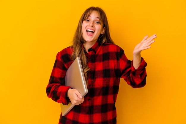 Young caucasian woman holding a laptop isolated receiving a pleasant surprise, excited and raising hands.
