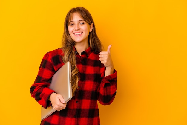 Young caucasian woman holding a laptop isolated smiling and raising thumb up