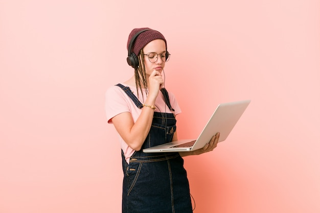 Young caucasian woman holding a laptop  sideways with doubtful and skeptical expression.