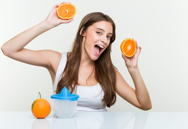 Young caucasian woman holding making an orange juice