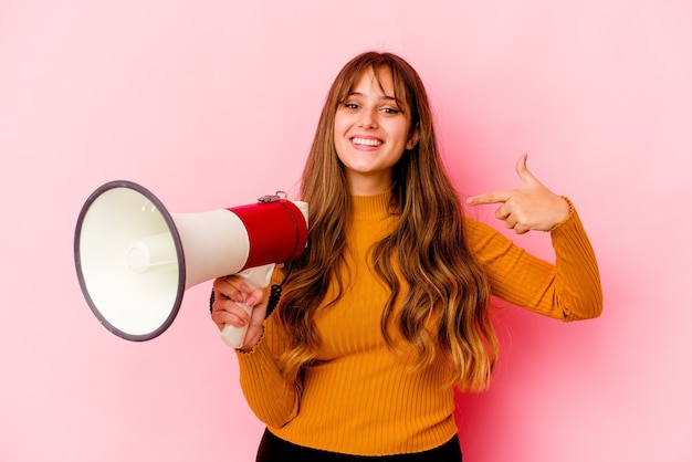 Young caucasian woman holding a megaphone isolated person pointing by hand to a shirt copy space, proud and confident