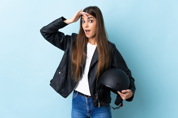 Young caucasian woman holding a motorcycle helmet isolated on blue doing surprise gesture while looking to the side