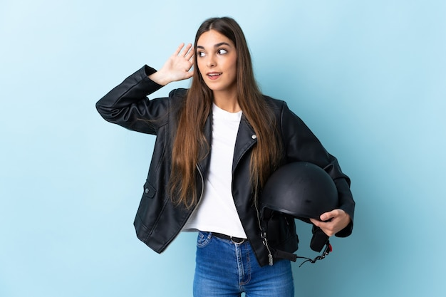 Young caucasian woman holding a motorcycle helmet isolated on blue listening to something by putting hand on the ear