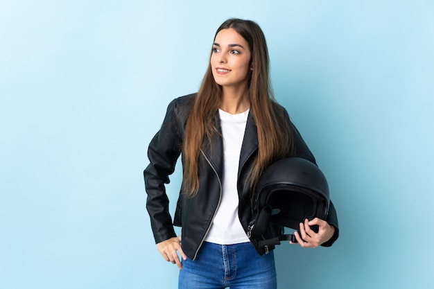 Young caucasian woman holding a motorcycle helmet isolated on blue looking to the side and smiling