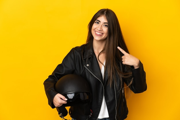 Young caucasian woman holding a motorcycle helmet isolated on yellow background giving a thumbs up gesture