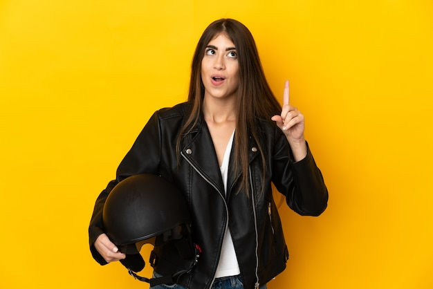 Young caucasian woman holding a motorcycle helmet isolated on yellow background intending to realizes the solution while lifting a finger up