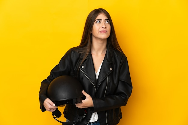 Young caucasian woman holding a motorcycle helmet isolated on yellow background and looking up