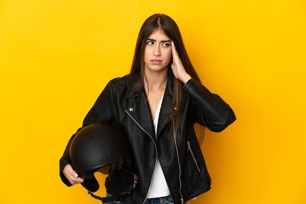 Young caucasian woman holding a motorcycle helmet isolated on yellow wall with headache
