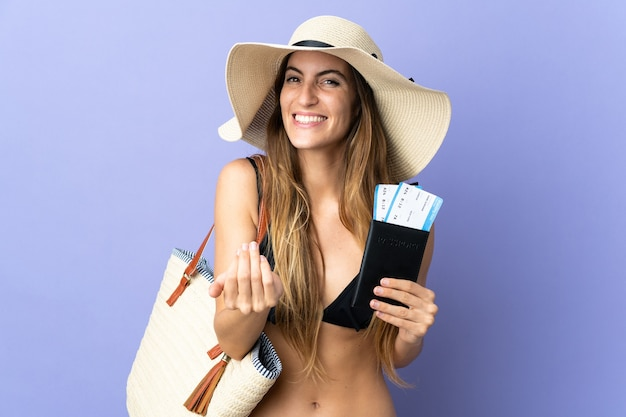 Young caucasian woman holding a passport for holidays isolated on purple background inviting to come with hand. happy that you came