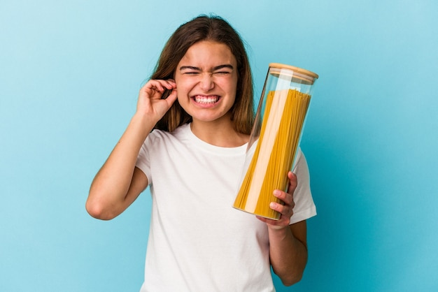 Young caucasian woman holding a pasta jar isolated on blue background covering ears with hands.