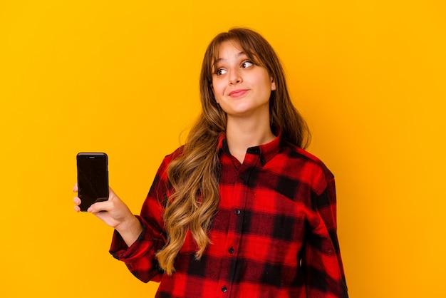 목표와 목적을 달성하는 꿈을 꾸고 노란색 벽에 고립 된 전화를 들고 젊은 백인 여자