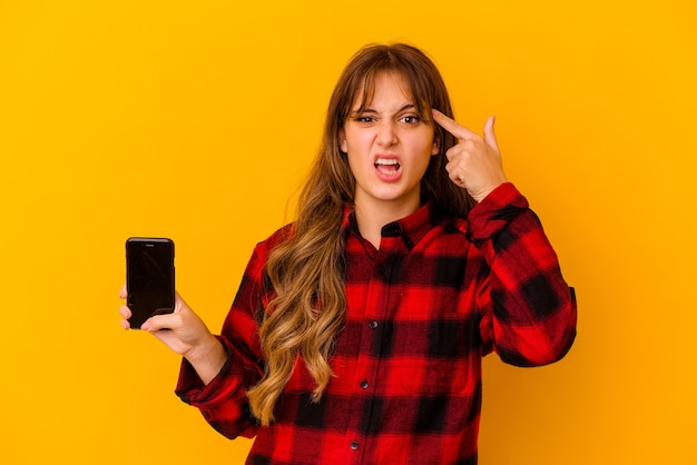 Young caucasian woman holding phone isolated on yellow wall showing a disappointment gesture with forefinger.