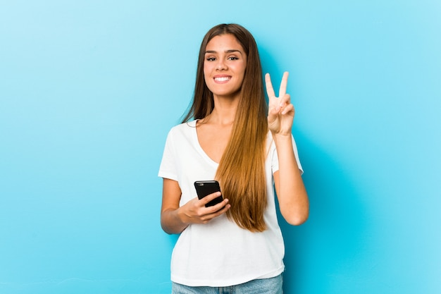 Young caucasian woman holding a phone showing number two with fingers.