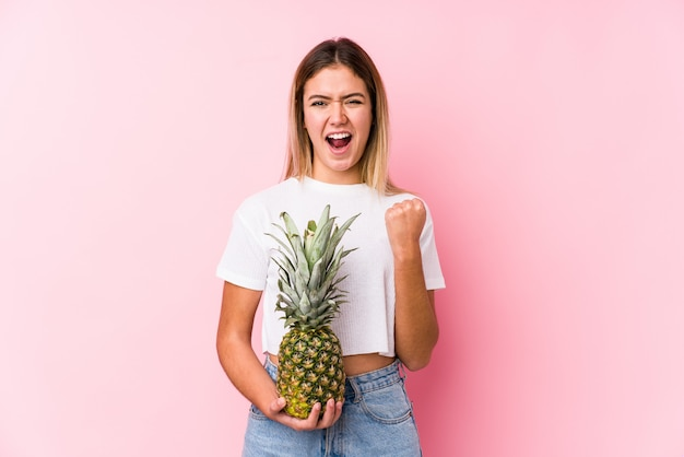 Young caucasian woman holding a pineapple cheering carefree and excited.