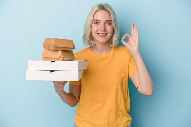 青い背景に分離されたピザやハンバーガーを持っている若い白人女性は、陽気で自信を持って大丈夫なジェスチャーを示しています。
