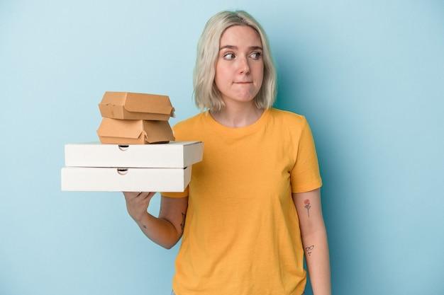 青い背景で隔離のピザやハンバーガーを保持している若い白人女性は混乱し、疑わしく、不安を感じています。