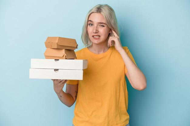 手で耳を覆う青い背景で隔離のピザやハンバーガーを保持している若い白人女性。