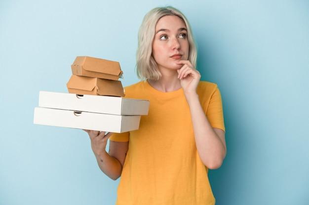 疑わしいと懐疑的な表情で横向きに青い背景で隔離のピザやハンバーガーを保持している若い白人女性。