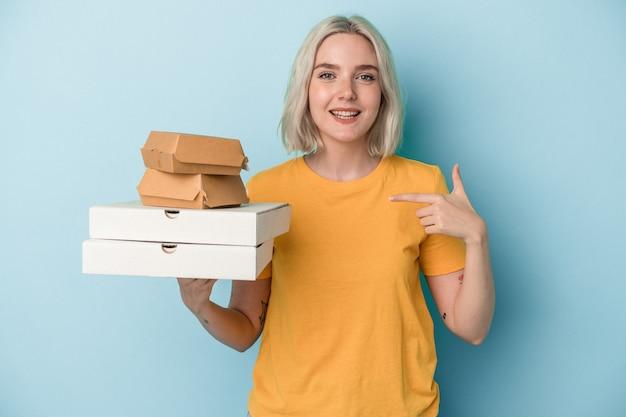 誇りと自信を持って、シャツのコピースペースを手で指している青い背景の人に分離されたピザやハンバーガーを保持している若い白人女性