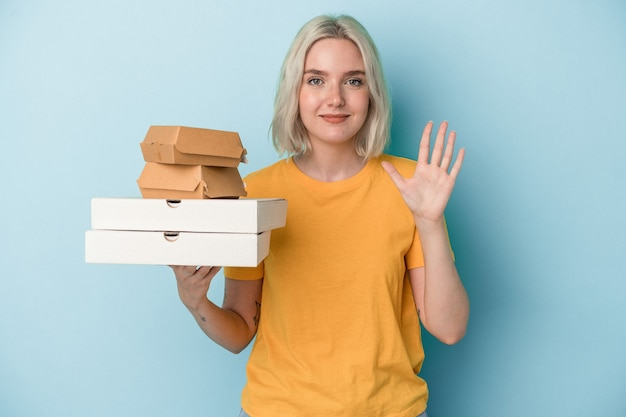 青い背景に分離されたピザやハンバーガーを持っている若い白人女性は、指で5番を示して陽気に笑っています。