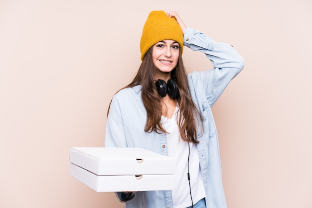 Young caucasian woman holding pizzas isolated being shocked, she has remembered important meeting.
